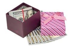 Dollar, die in rote verzierte Geschenkbox legen Lizenzfreie Stockfotos