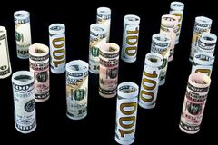 Dollar. Dollar banknotes roll in other positions. American US currency on black board. American dollar banknote rolls. In all denominations isolated on black royalty free stock image