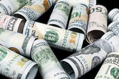 Dollar. Dollar banknotes roll in other positions. American US currency on black board. American dollar banknote rolls. In all denominations isolated on black stock photos