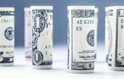 Dollar. Dollar banknotes roll in other positions. American US currency on white board and defocused background Stock Image