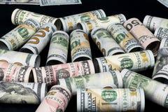 dollar Dollarsedelrulle i annan positioner Amerikansk USA-valuta på svart bräde Amerikanska dollarsedelrullar Arkivbilder