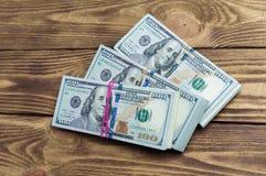 Dollar in drei Sätzen auf einem Holztisch Lizenzfreie Stockfotografie