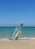 10 Dollar in einer Flasche auf dem Sand Stockfotografie