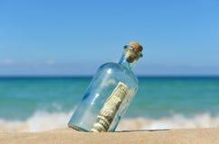 10 Dollar in einer Flasche auf dem Strand Stockbild
