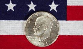 Dollar en argent d'Eisenhower sur le drapeau américain Image stock