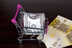 Dollar and Euro Banknotes with Shopping Cart Consuming Concept Royalty Free Stock Photos