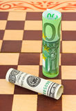 Dollar and euro on chess board Royalty Free Stock Image