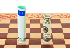 Dollar and euro on chess board Royalty Free Stock Images