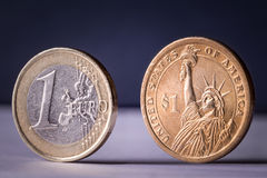 Dollar euro coins. 1 euro 1 dollar coins separated on blue background Royalty Free Stock Photos