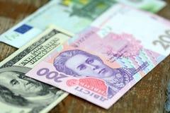Dollar euro- och hryvniasedlar på träbakgrund Arkivbild
