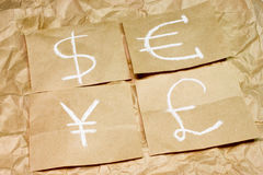 Dollar, euro, pound and yen currency icons on paper. Royalty Free Stock Photography