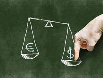 The dollar and the euro on the scales drawn on the Blackboard wi Stock Photo