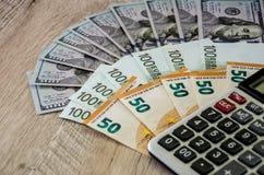 Dollar, Euro und und Taschenrechner auf hölzernem Hintergrund lizenzfreie stockbilder