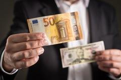 Dollar gegen Euro Geschäftsmann in der Klage, die Banknote 50 hält Stockfotografie