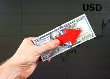 Dollar Grow Concept. Red Arrow in a Hand with the Dollars on the Diagram Background Stock Photos