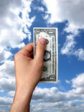 Dollar at hand. One dollar at hand on cloudy background Royalty Free Stock Images