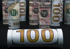Dollar Het broodje van dollarbankbiljetten in andere posities De Amerikaanse munt van de V.S. op zwarte raad De Amerikaanse brood Royalty-vrije Stock Foto's