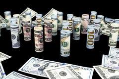 Dollar Het broodje van dollarbankbiljetten in andere posities De Amerikaanse munt van de V.S. op zwarte raad De Amerikaanse brood Stock Fotografie