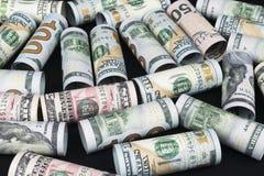 Dollar Het broodje van dollarbankbiljetten in andere posities De Amerikaanse munt van de V.S. op zwarte raad De Amerikaanse brood Stock Foto