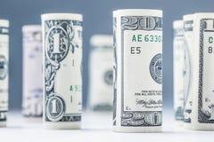 Dollar Het broodje van dollarbankbiljetten in andere posities De Amerikaanse munt van de V.S. op witte raad en defocused achtergr Stock Fotografie