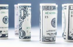 Dollar Het broodje van dollarbankbiljetten in andere posities De Amerikaanse munt van de V.S. op witte raad en defocused achtergr Stock Afbeelding