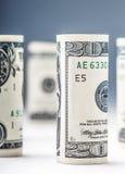 Dollar Het broodje van dollarbankbiljetten in andere posities De Amerikaanse munt van de V.S. op witte raad en defocused achtergr Royalty-vrije Stock Fotografie