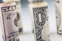 Dollar Het broodje van dollarbankbiljetten in andere posities De Amerikaanse munt van de V.S. op witte raad en defocused achtergr Stock Afbeeldingen