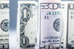 Dollar Het broodje van dollarbankbiljetten in andere posities De Amerikaanse munt van de V.S. op witte raad en defocused achtergr Stock Foto