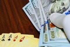 Dollar holded i hand över poker som spelar kort Royaltyfria Bilder