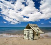 Dollar house on sand. Stock Photos