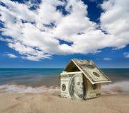Dollar house on sand. Stock Photos