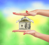 Dollar house on woman hand over nature Royalty Free Stock Image