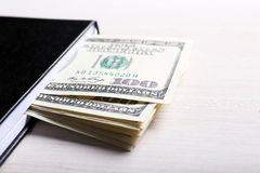 Dollar i anteckningsbok på ljus träbakgrund Arkivfoton
