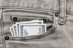 Dollar i grått jeanfack Arkivbild
