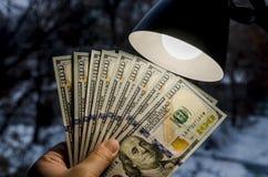 Dollar i hand och en tabelllampa royaltyfri fotografi