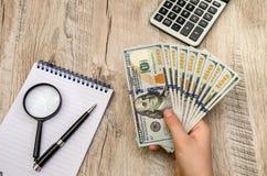 Dollar i hand, räknemaskin, notepad och penna royaltyfria bilder