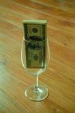 Dollar im Weinglas Stockfotografie
