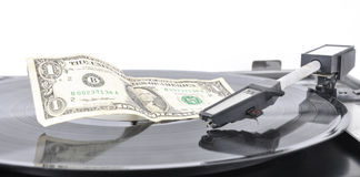 A dollar lying on an old record player on a plate Royalty Free Stock Photos