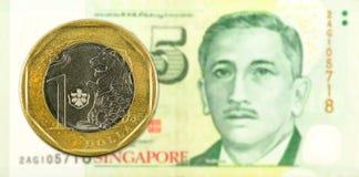 1-Dollar-Münze gegen 5 Singapur Dollar-Banknotengegenstücck Stockfotografie