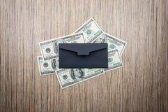 Dollar med det svarta kuvertet på trätabellen Top beskådar royaltyfria foton