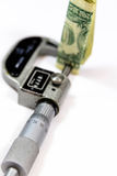 Dollar in a micrometer guage to measure thickness Stock Photos