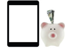100 dollar money inside pink piggy bank next to tablet computer. American 100 dollar currency money inside pink piggy bank next to black tablet computer with Stock Image
