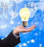 Dollar money sign in light bulb. On hand of business man , ideal for global financial concept stock image