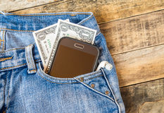Dollar money and smart phone in pocket blue jeans Royalty Free Stock Photo