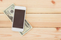 Dollar money with your smartphone on wooden table. Top view with copy space. Online shopping concept Royalty Free Stock Images