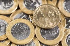 1 dollar mynt i mitt av flera verkliga mynt 1 på ett trä Arkivbilder