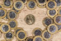 1 dollar mynt i mitt av flera verkliga mynt 1 på ett trä Royaltyfri Foto