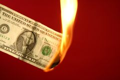 Dollar note burning in fire over red Stock Image