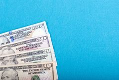 Dollar notes, folded fan, top view, blue background Stock Photos