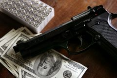 Dollar notes and gun, black pistol Stock Photos